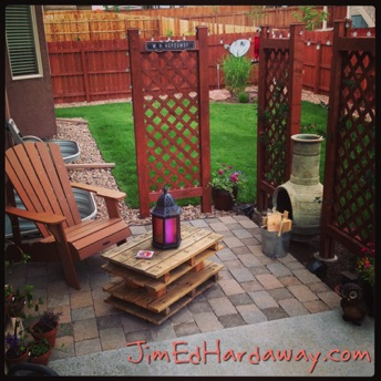 Backyard Sitting Area. Adirondack chair, pavers, chiminea, trellises with honeysuckle vines, flower bed and pots, and pallet table with decor. Now, all you need is a glass of sweet tea and a good book or sketchpad!